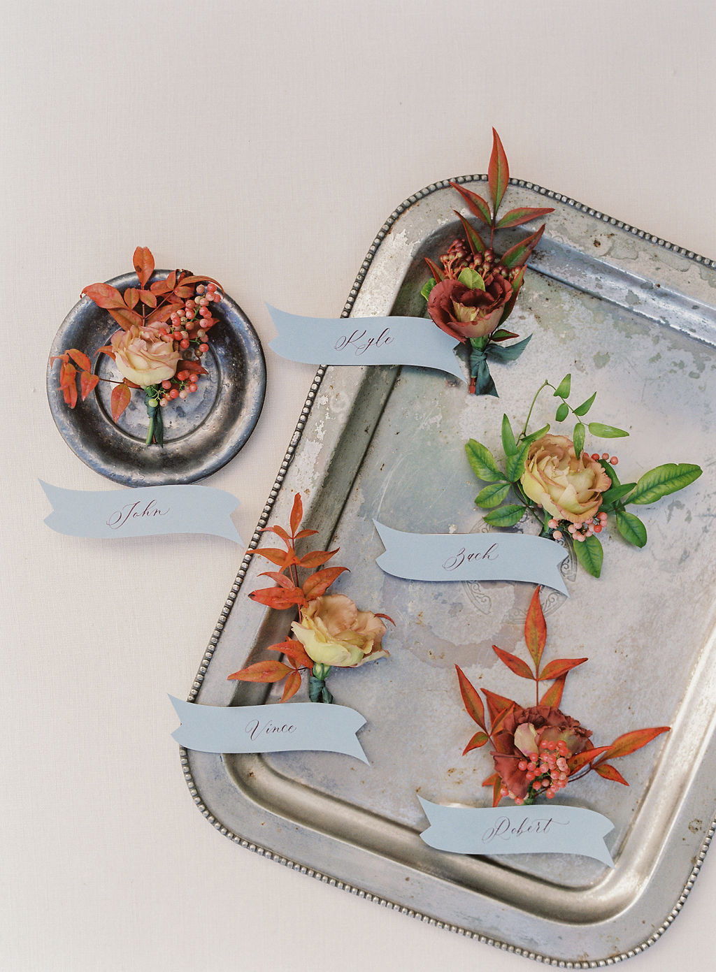 fall colored wedding boutonnières on silver tray