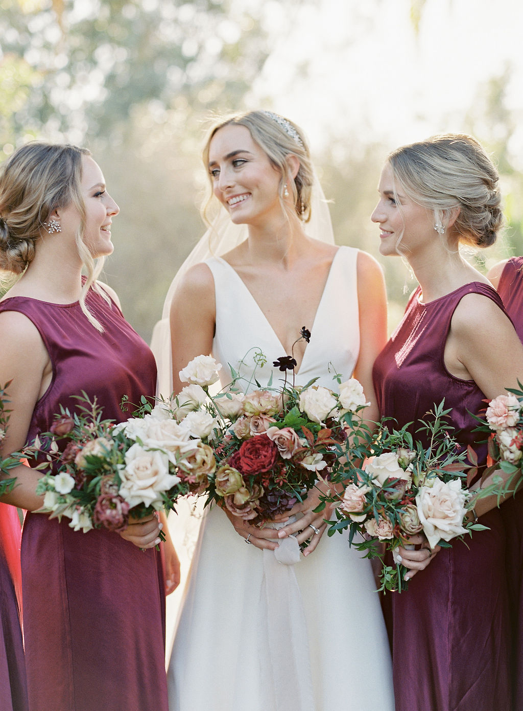 bride with bridesmaids in maroon dresses