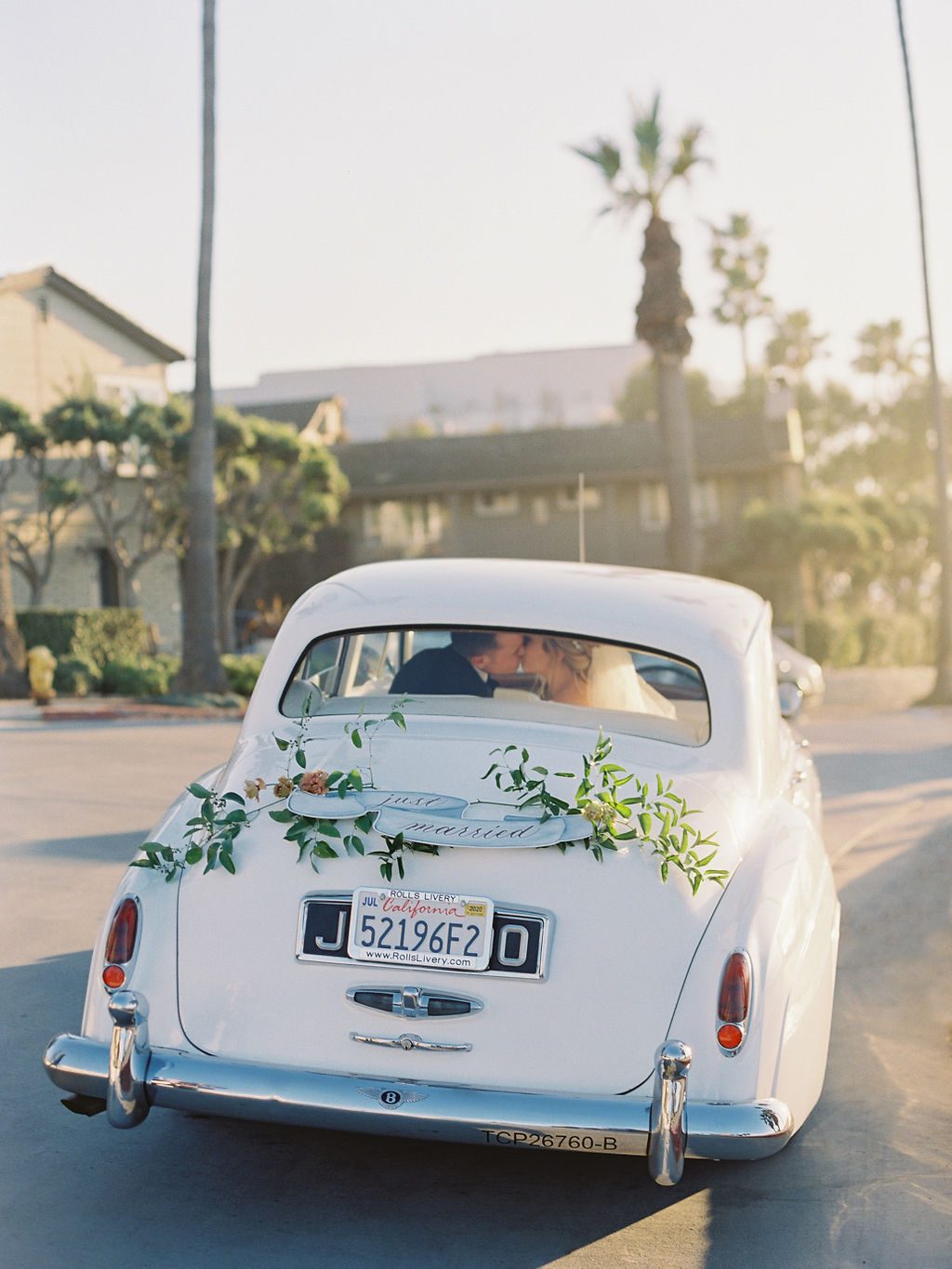couple driving away in white vintage car with just married sign