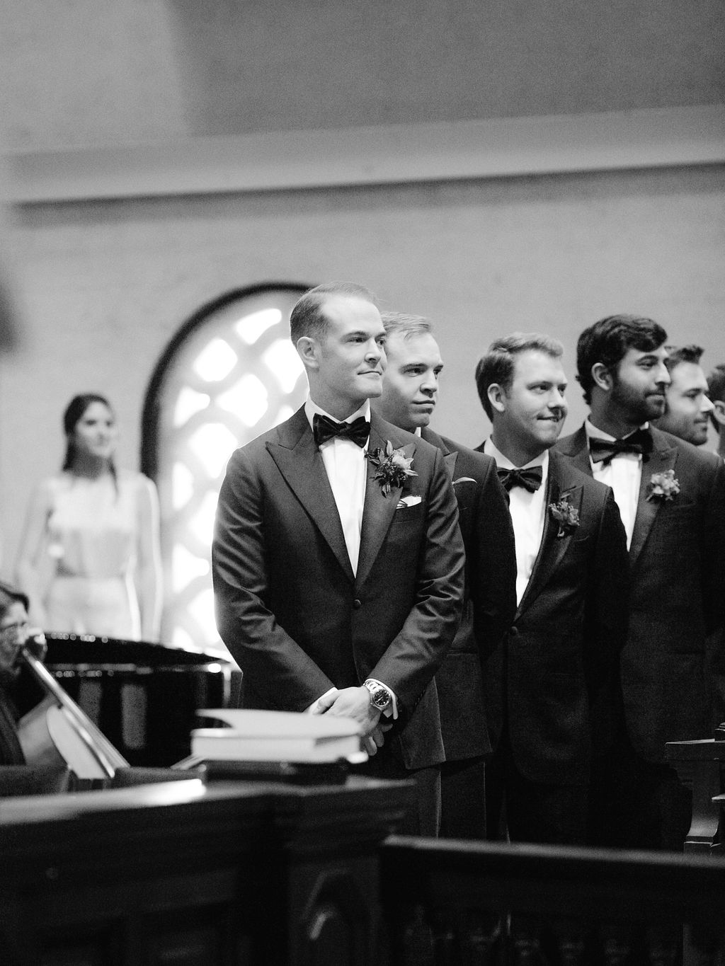 groom and groomsmen standing in tuxes at wedding ceremony