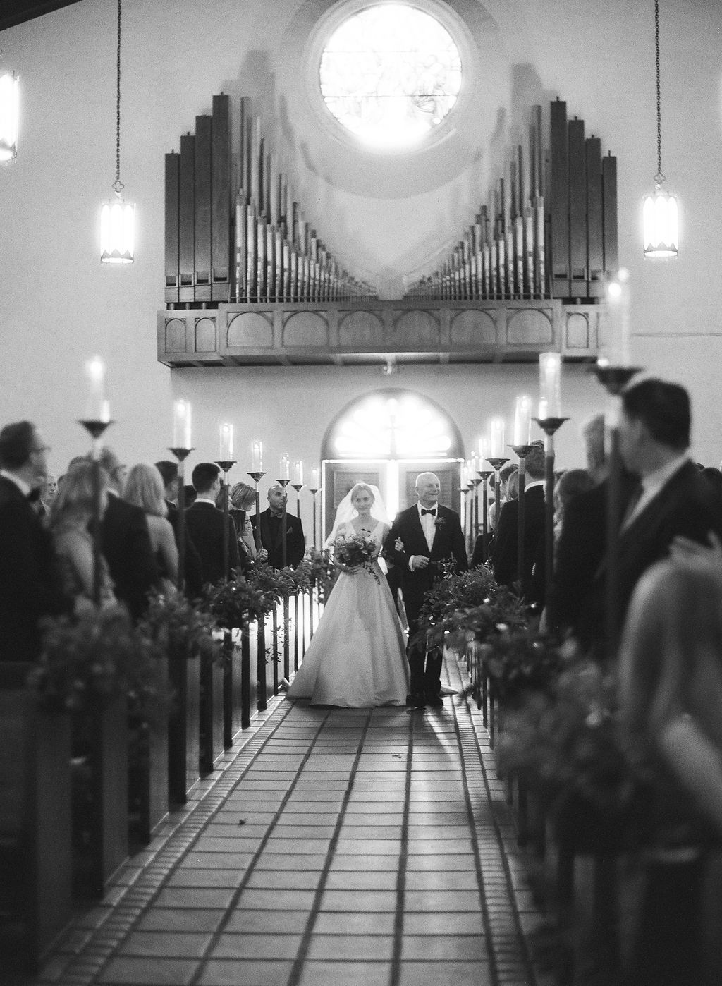 bride and father entering church with sunlight spilling in behind