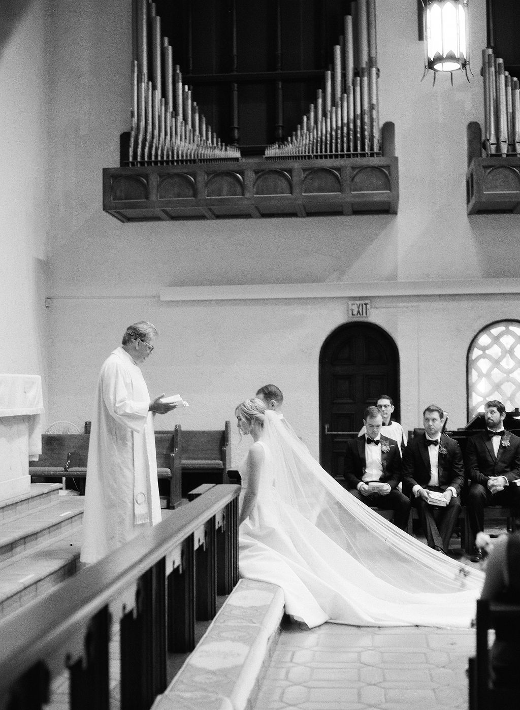 bride and groom kneeling during religious wedding ceremony in church