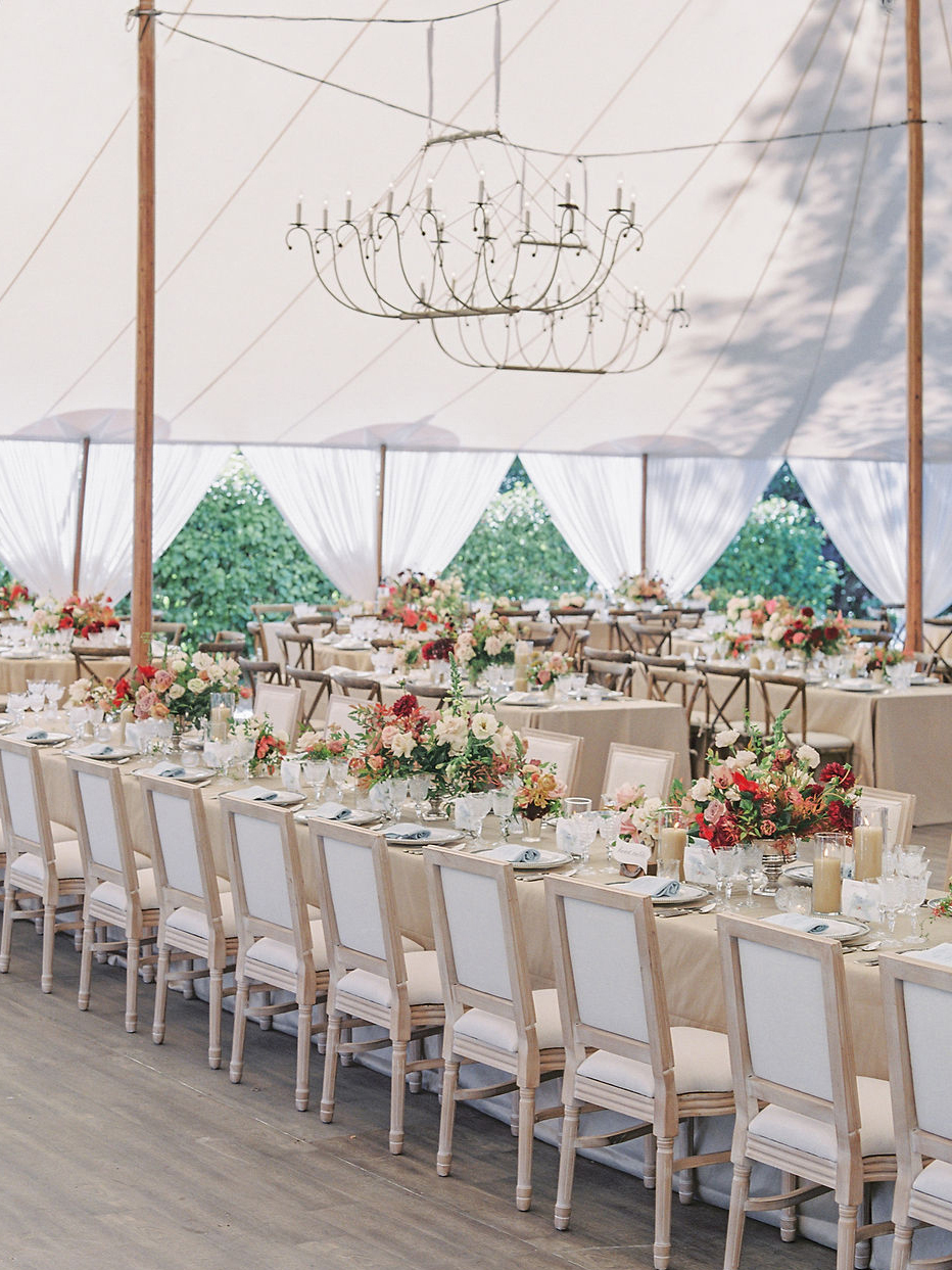 elegant long neutral and fall tones tables inside wedding reception tent
