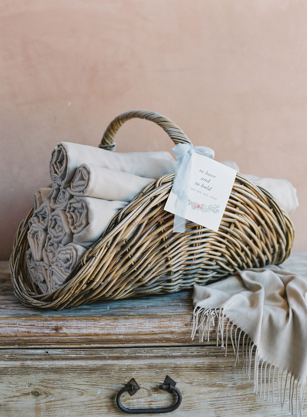 wicker basket of tan blankets for guests
