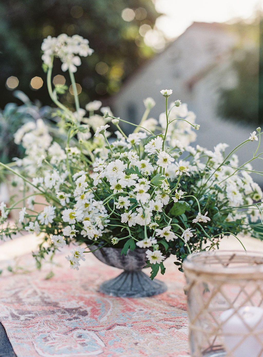 white wildflowers in metal vase on spanish rug
