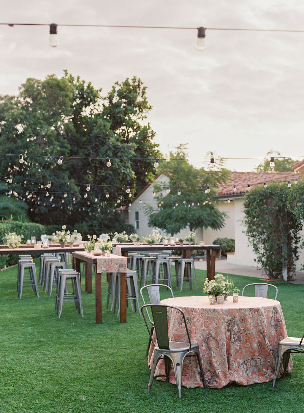 outdoor welcome party on lawn with wooden tables and metal chairs