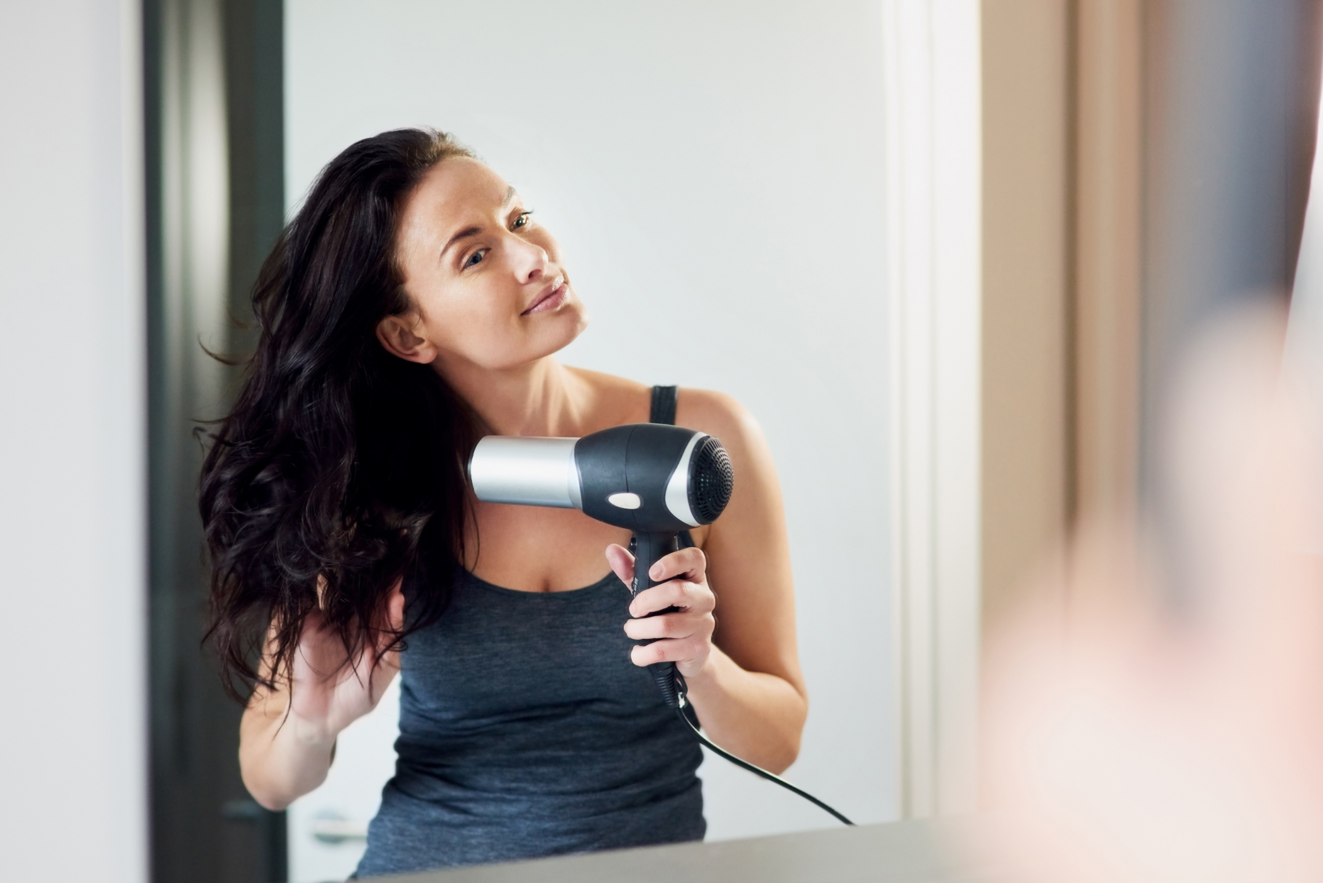 woman blow drying hair in mirror