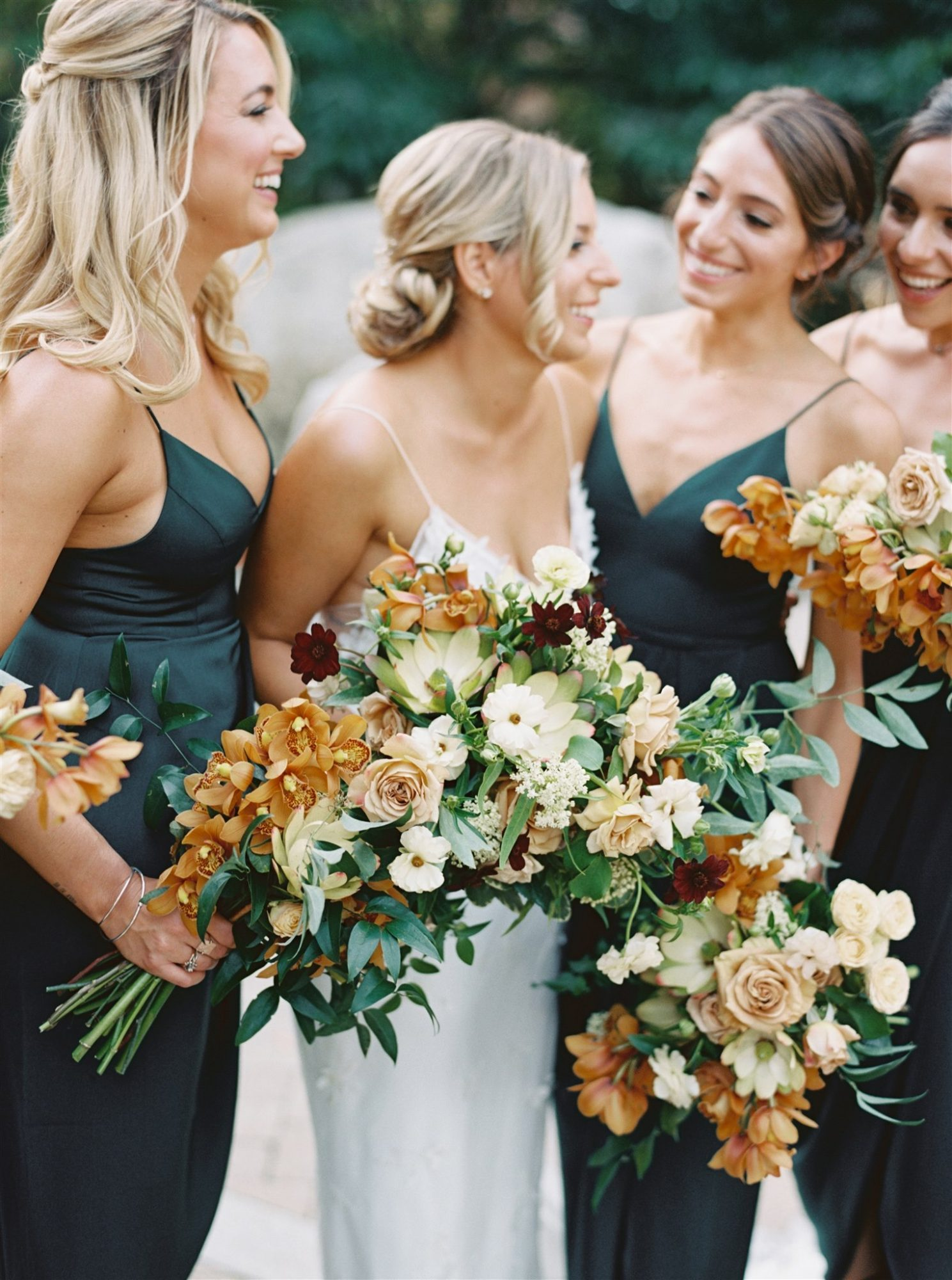brianna with bridesmaids holding fall-colored bouquets