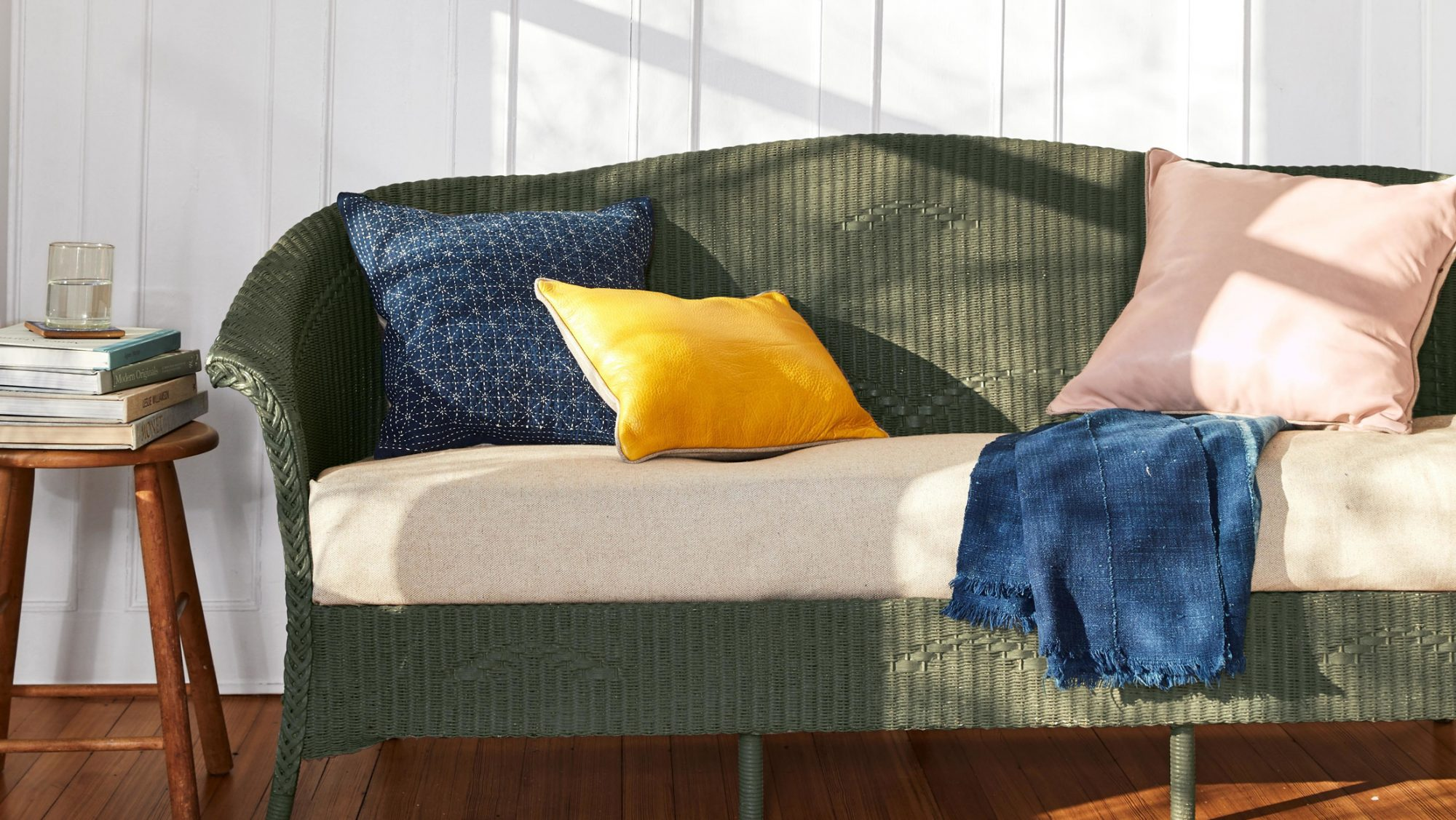 olive green painted wicker sofa with throw pillows
