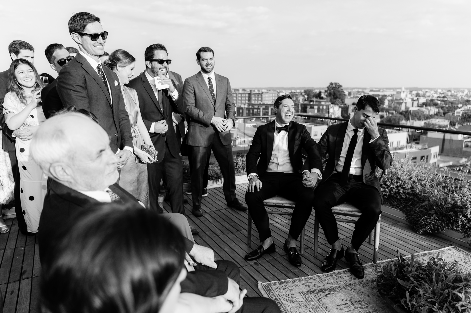 wedding couple seated on rooftop surrounded by guests