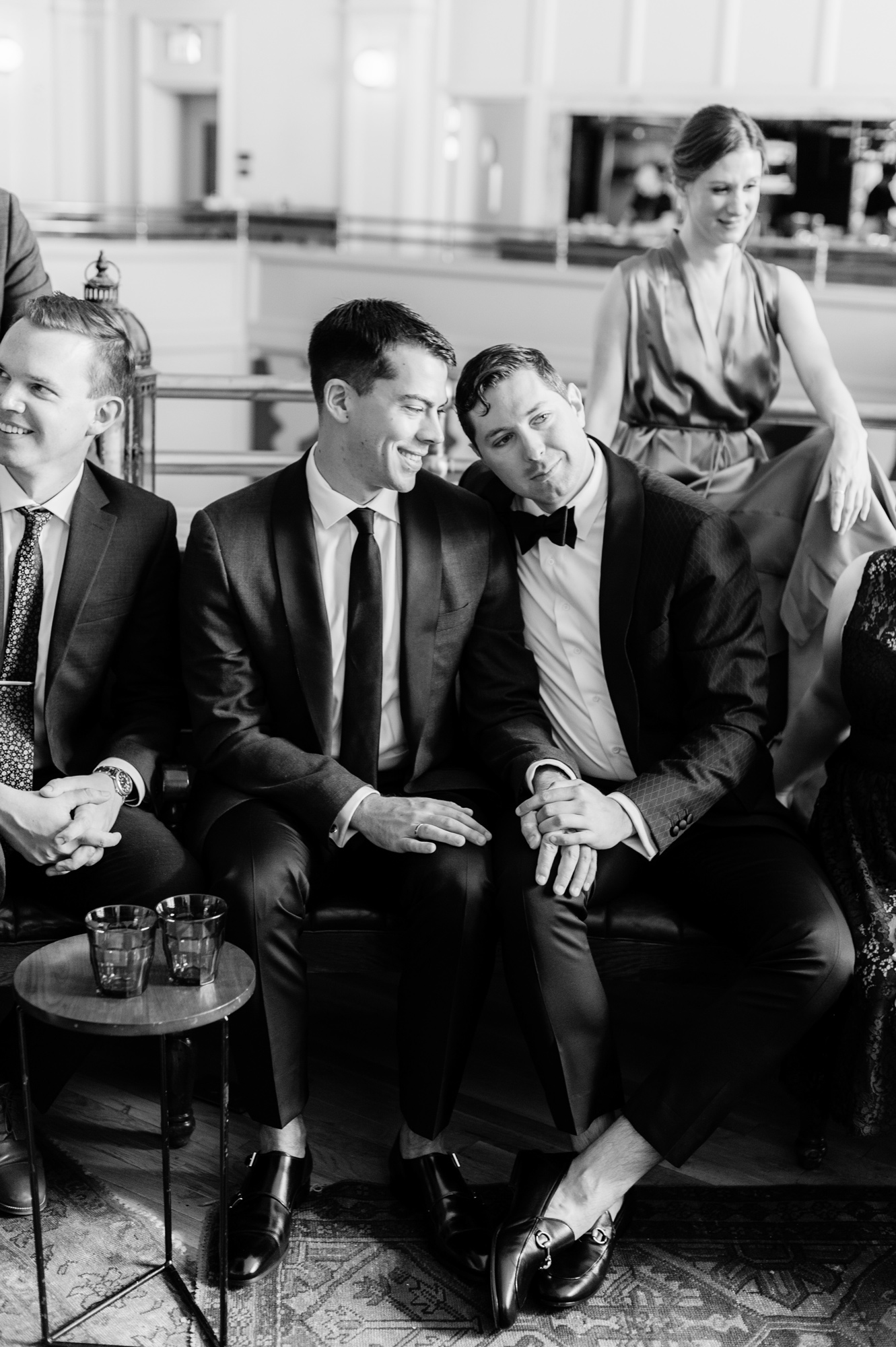 black and white portrait of wedding couple sitting among guests