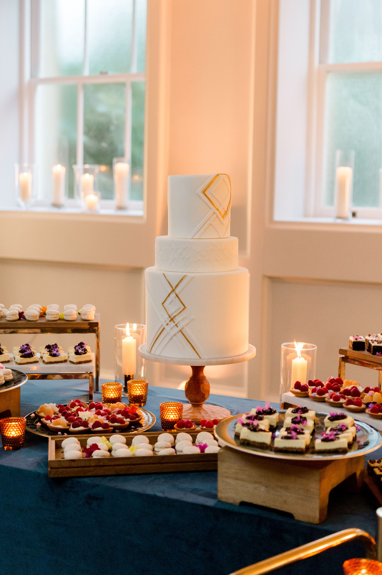three tier wedding cake surrounded by finger-food desserts