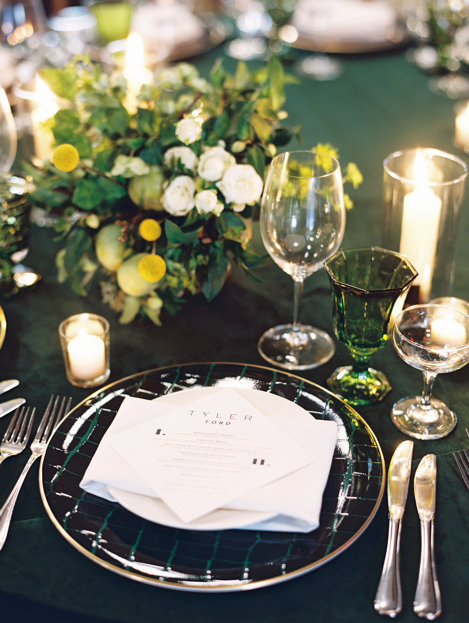 close-up of green place setting white and yellow floral centerpiece