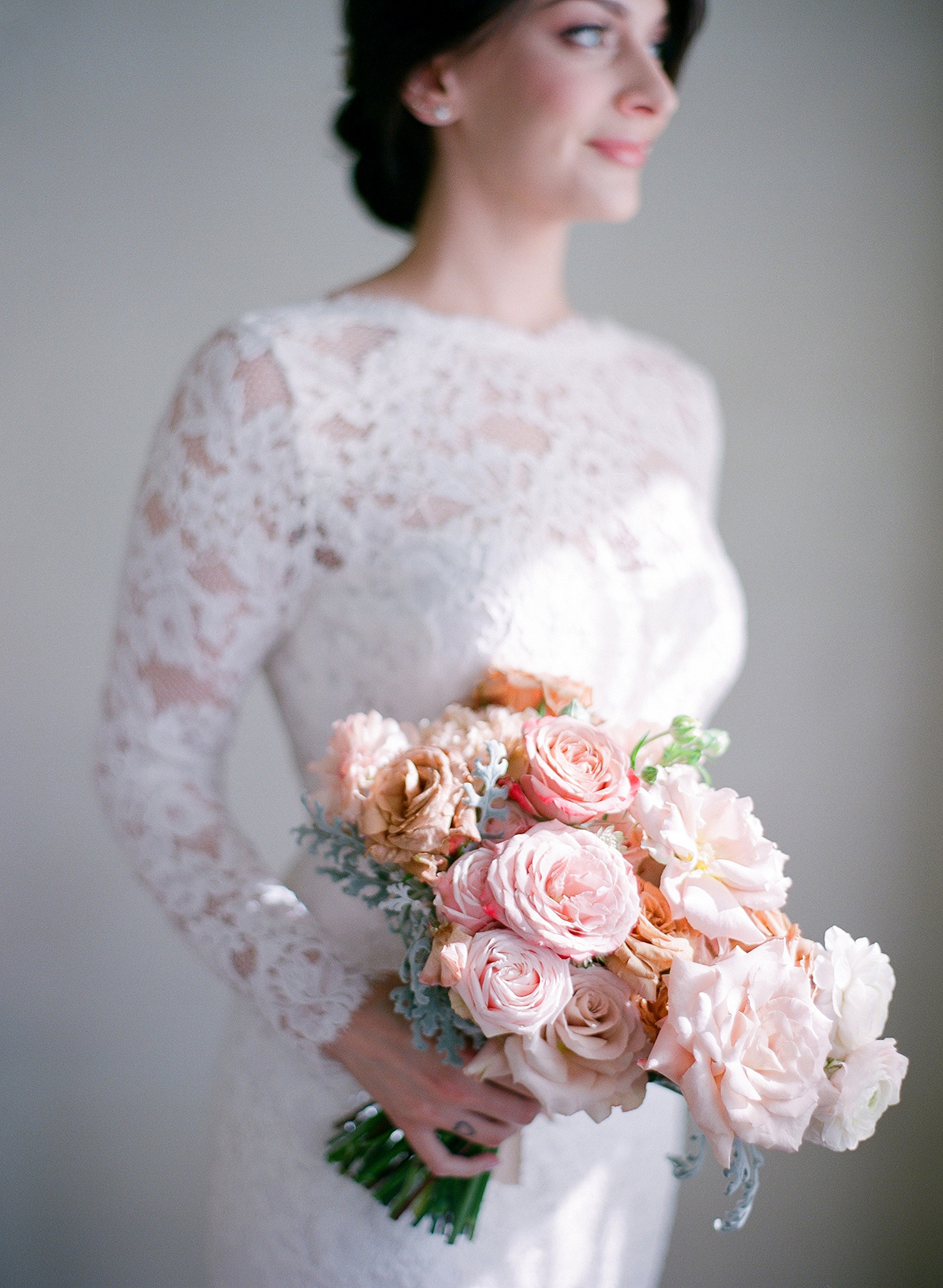 bride in white lace dress holding pastel rose bouquet