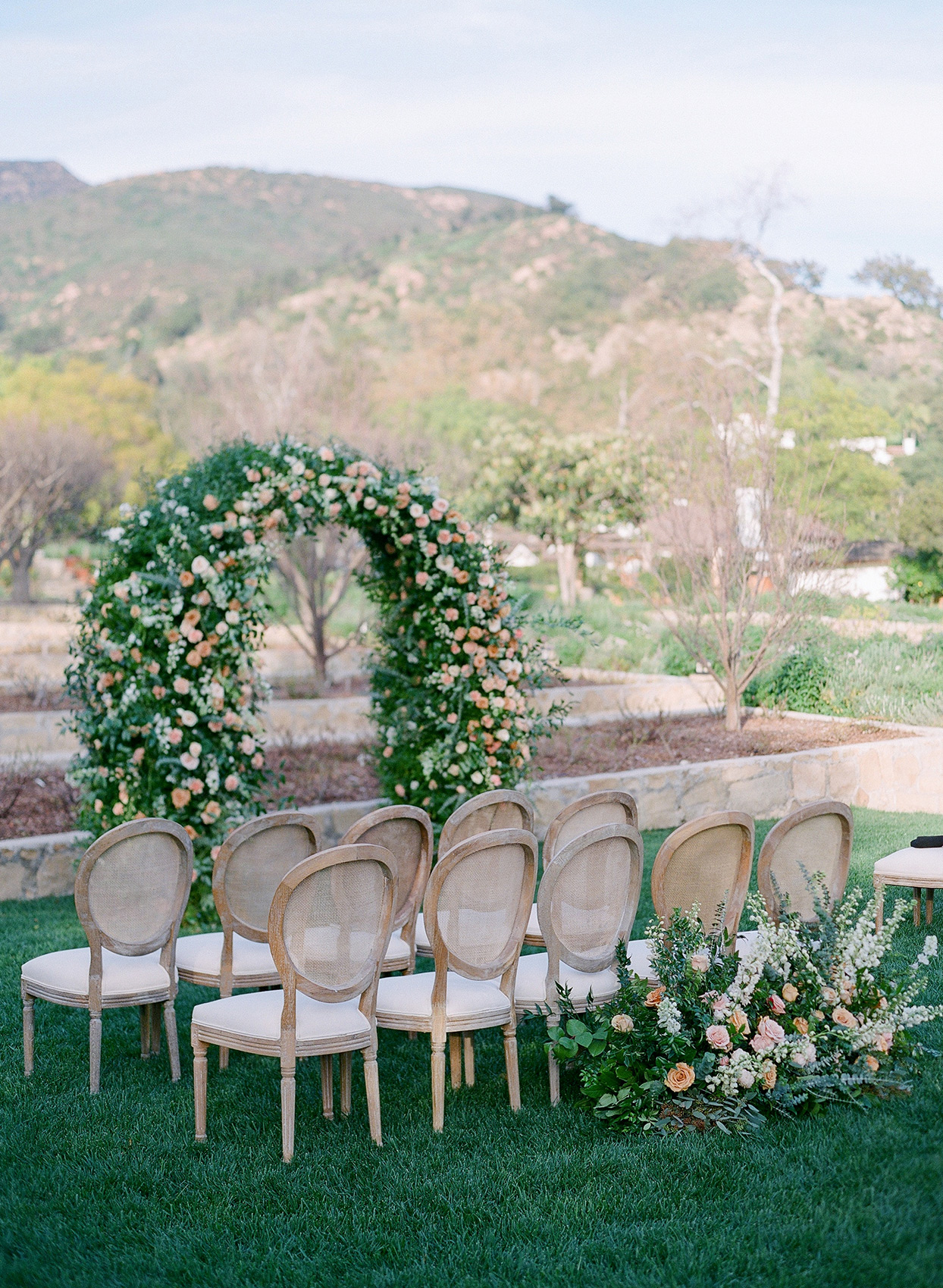 wooden chairs set up for outdoor ceremony with mountain backdrop