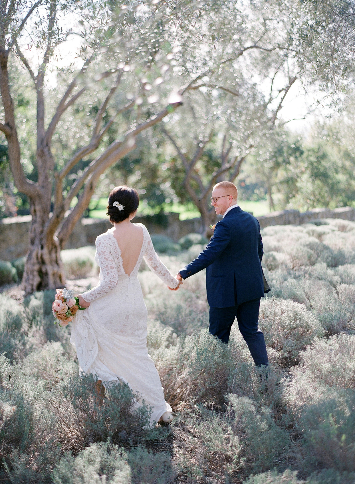 couple walking through wild grasses during portrait session
