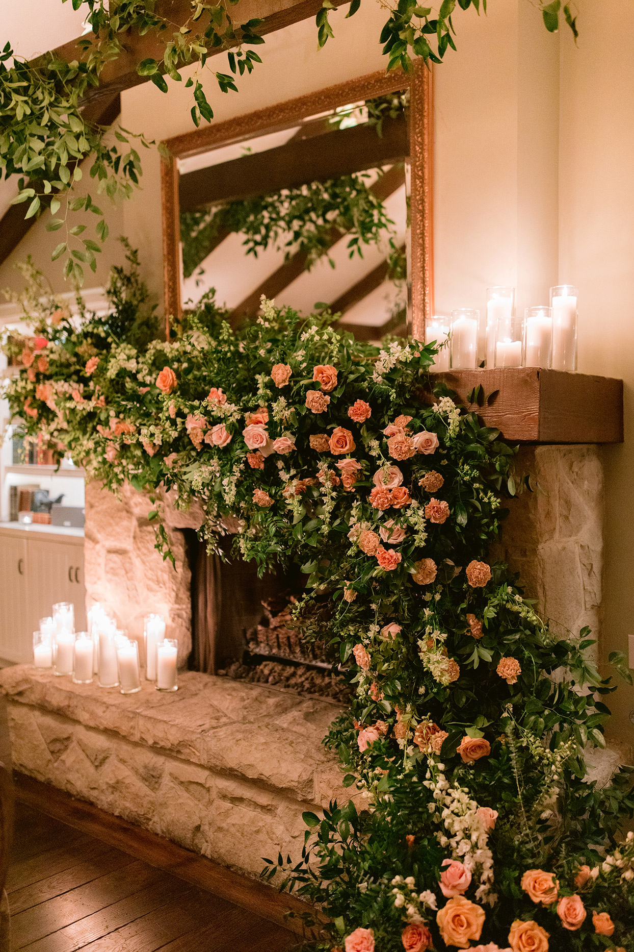wedding fireplace with elaborate floral garland and candles