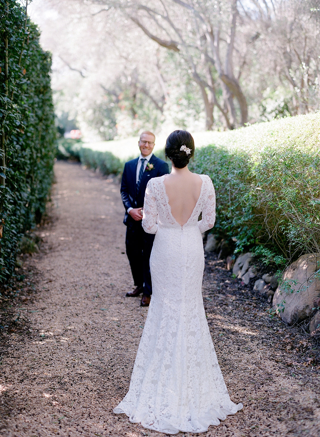 bride standing on gravel with while groom smiles at her during first look