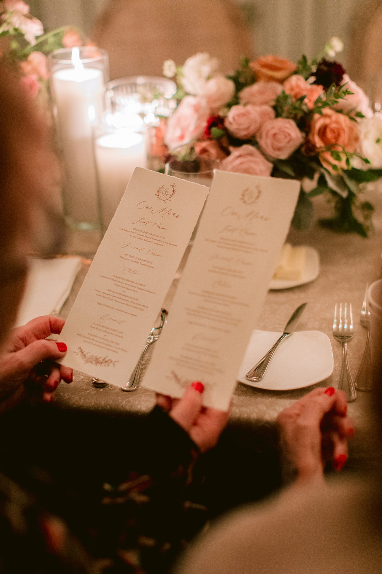 guests holding wedding menus at reception tables under candle light