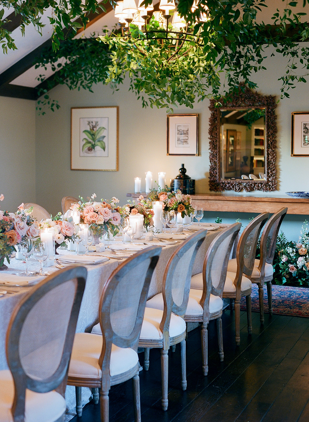 reception long table under lamp chandelier decorated in greenery