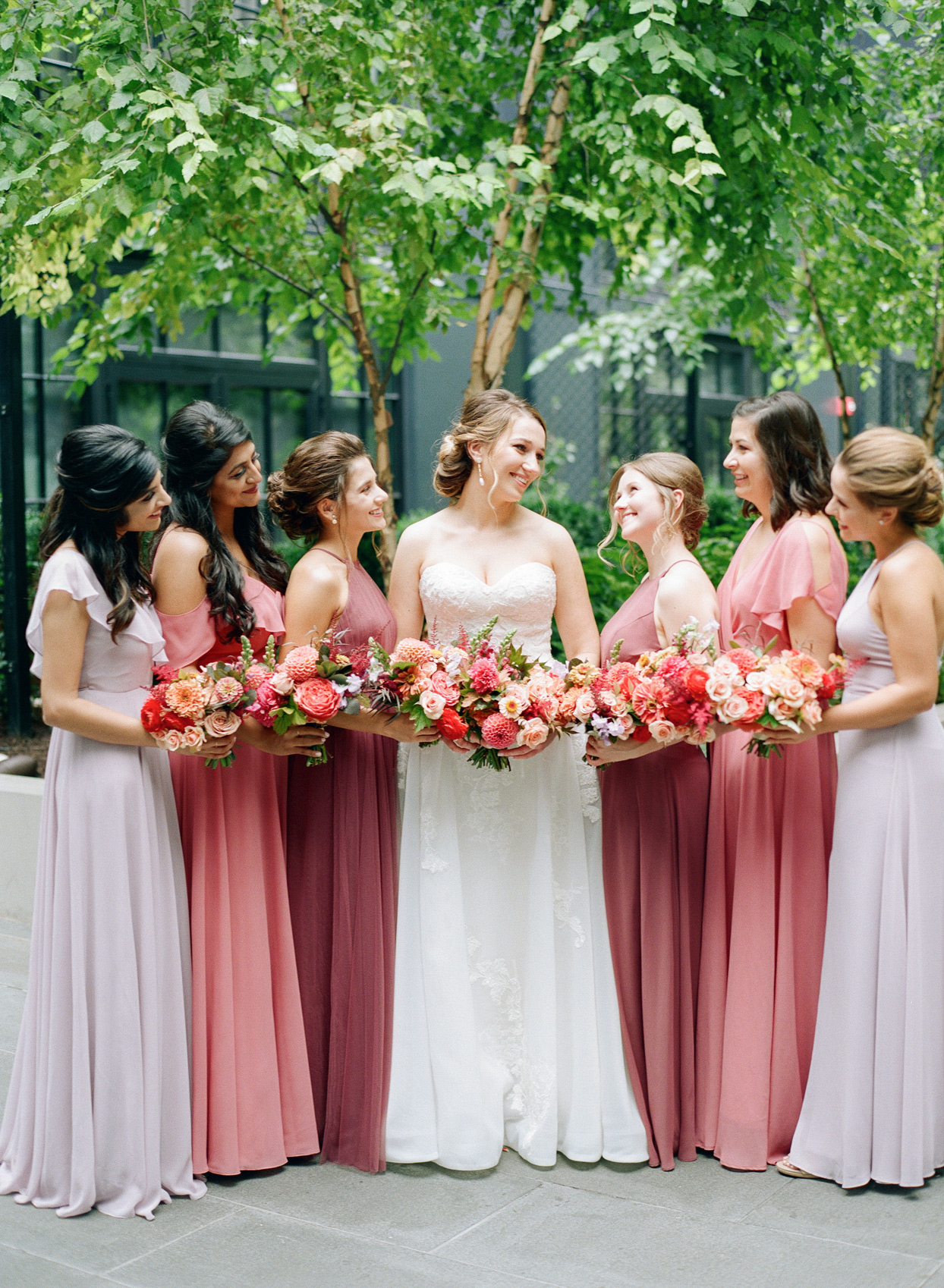 bride with bridesmaids in lilac and pink dresses