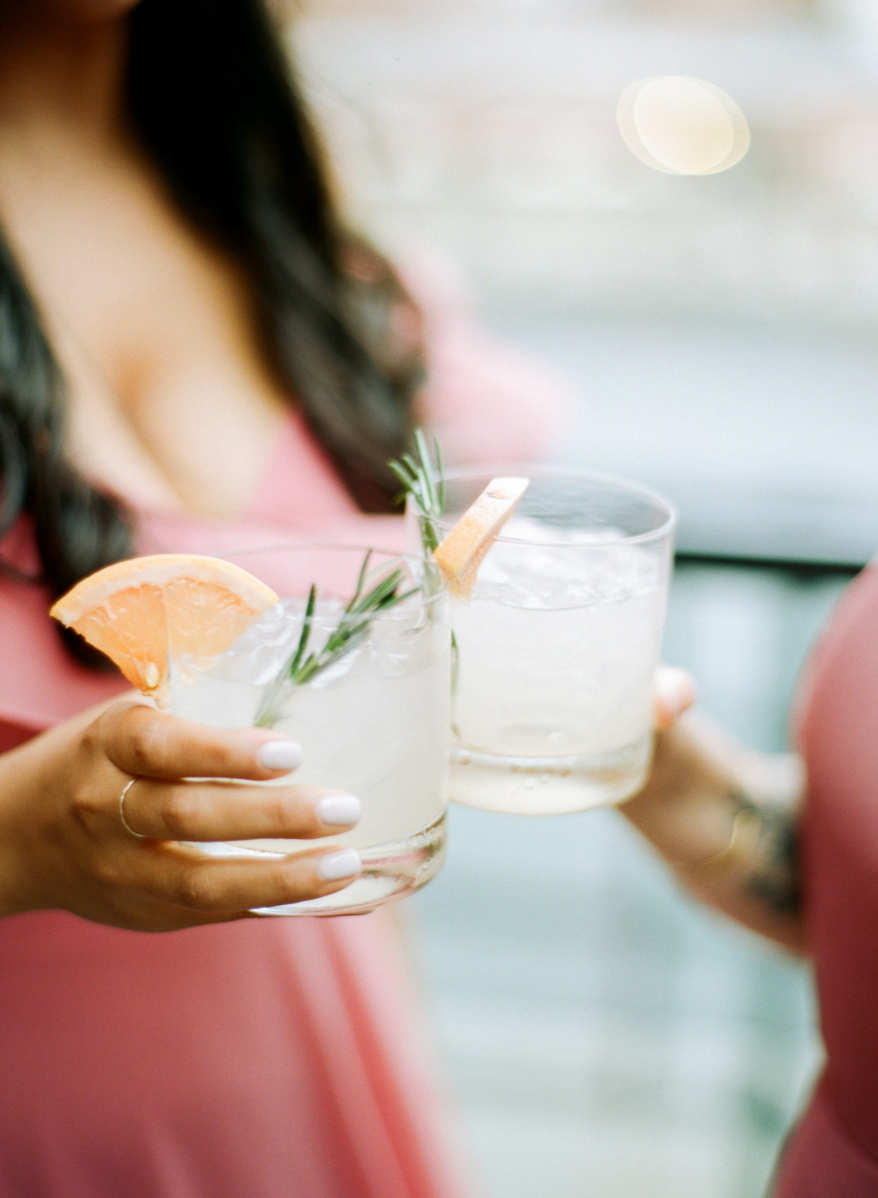 women clinking grapefruit and rosemary cocktails