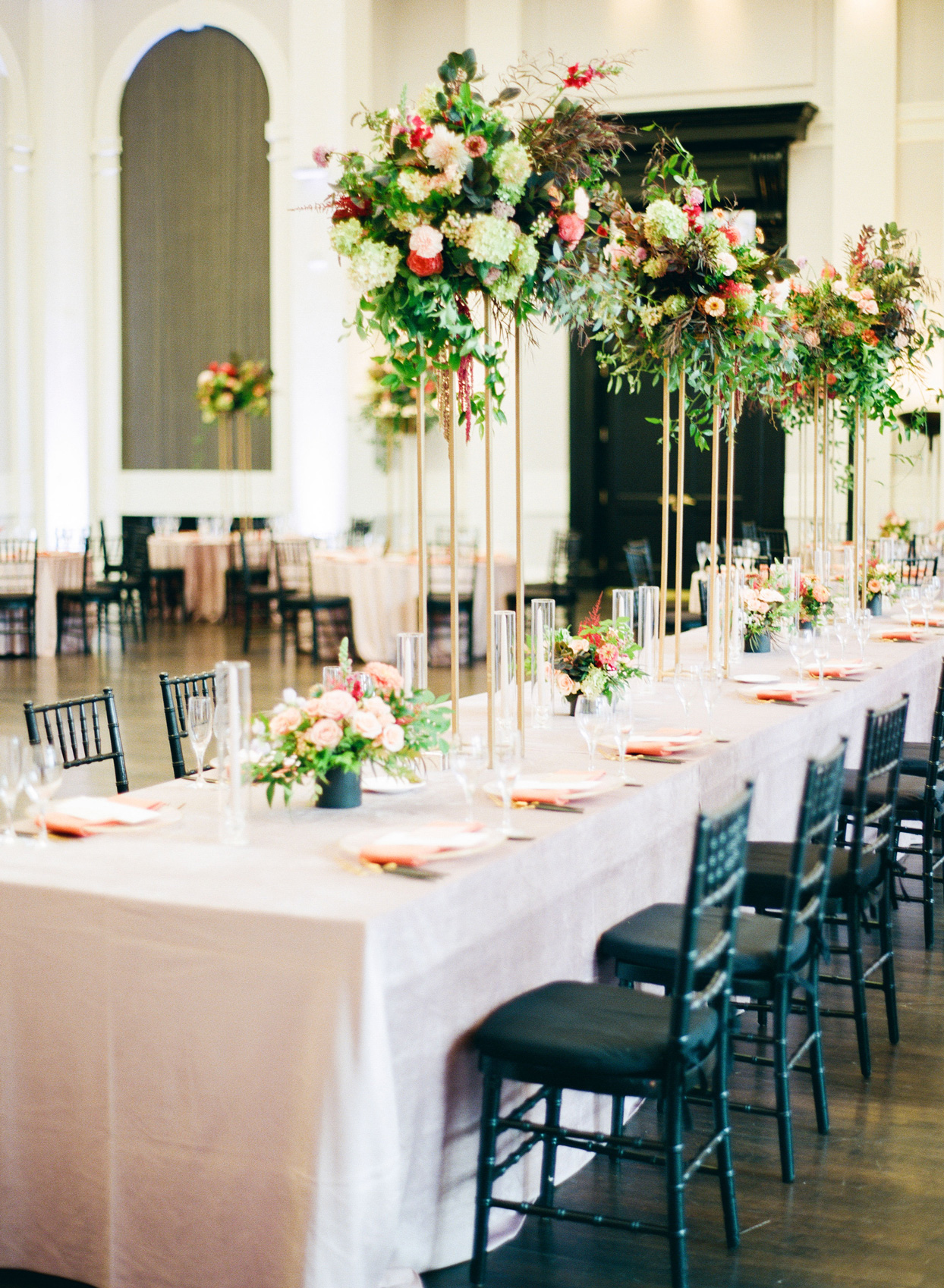 wedding reception ballroom with tall floral centerpieces