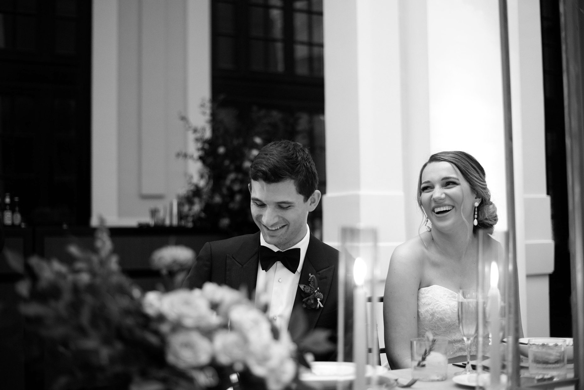 bride and groom smiling while sitting at table