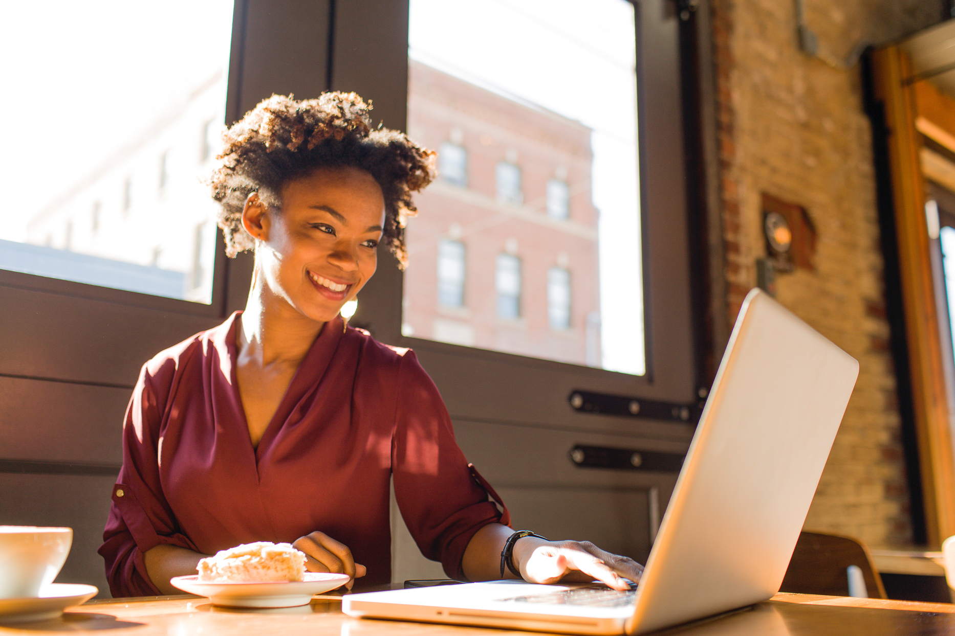 woman smiling looking down at laptop