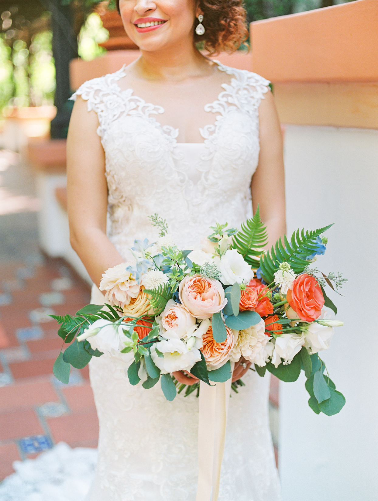 bride smiling holding garden-style oblong bouquet