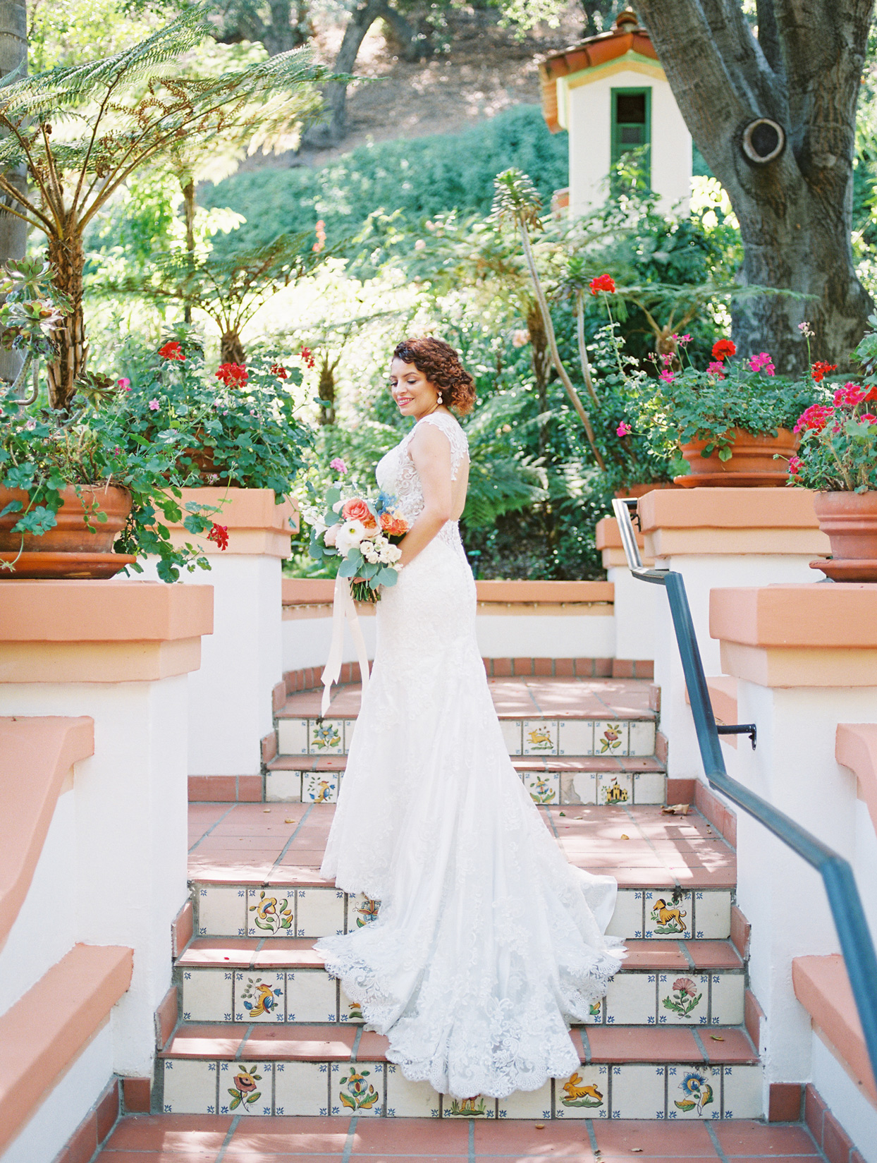 bride wearing lace train wedding dress on tiled stairway outside