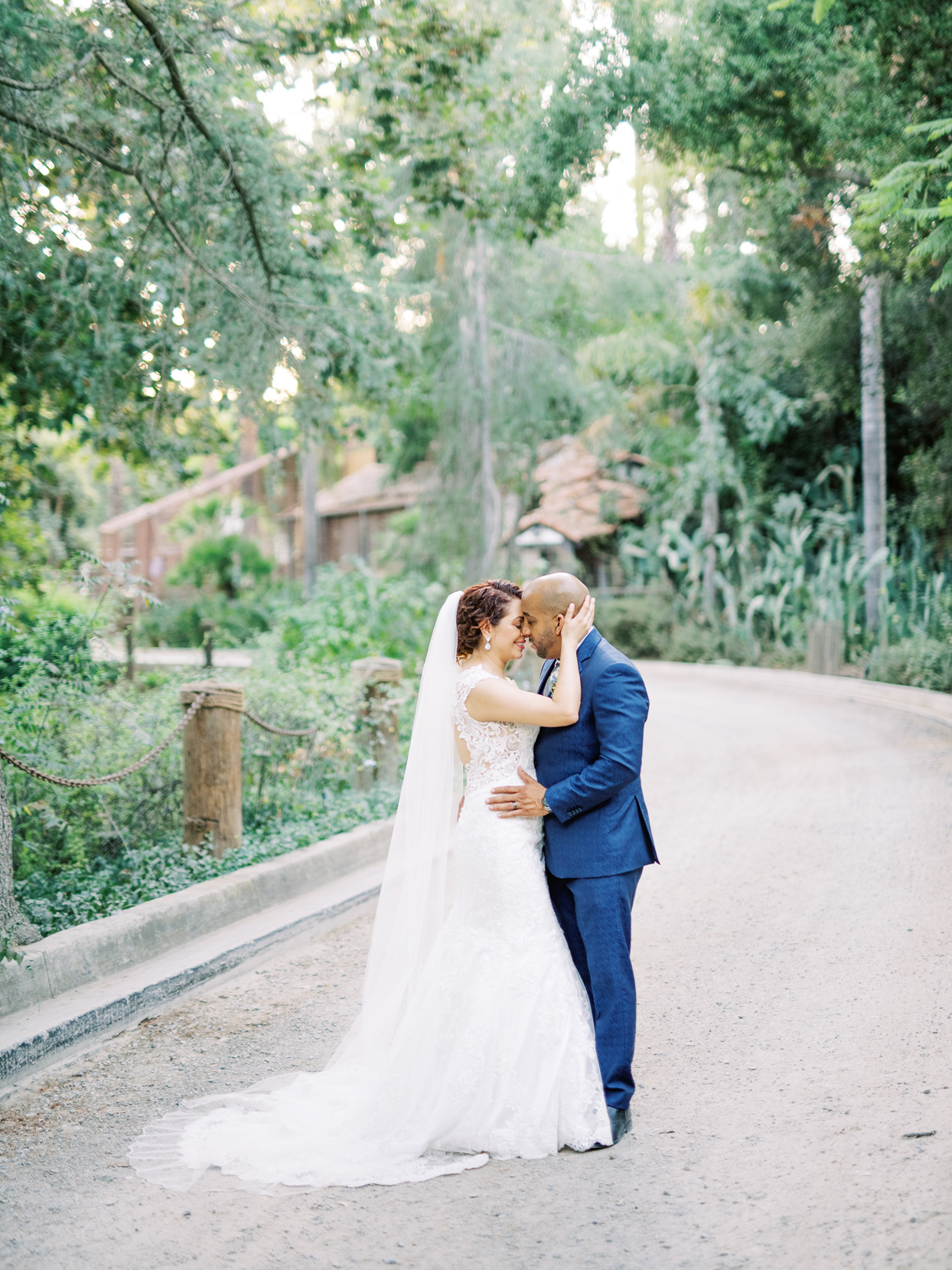 bride and groom embrace outside on pathway