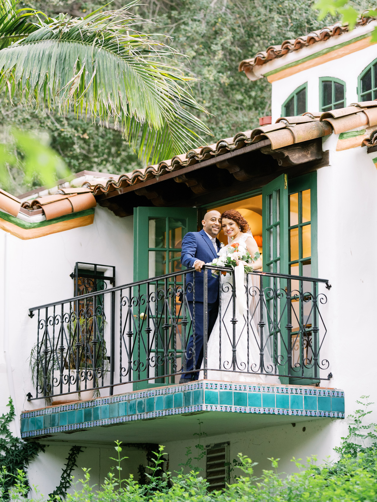 bride and groom stand smiling on balcony