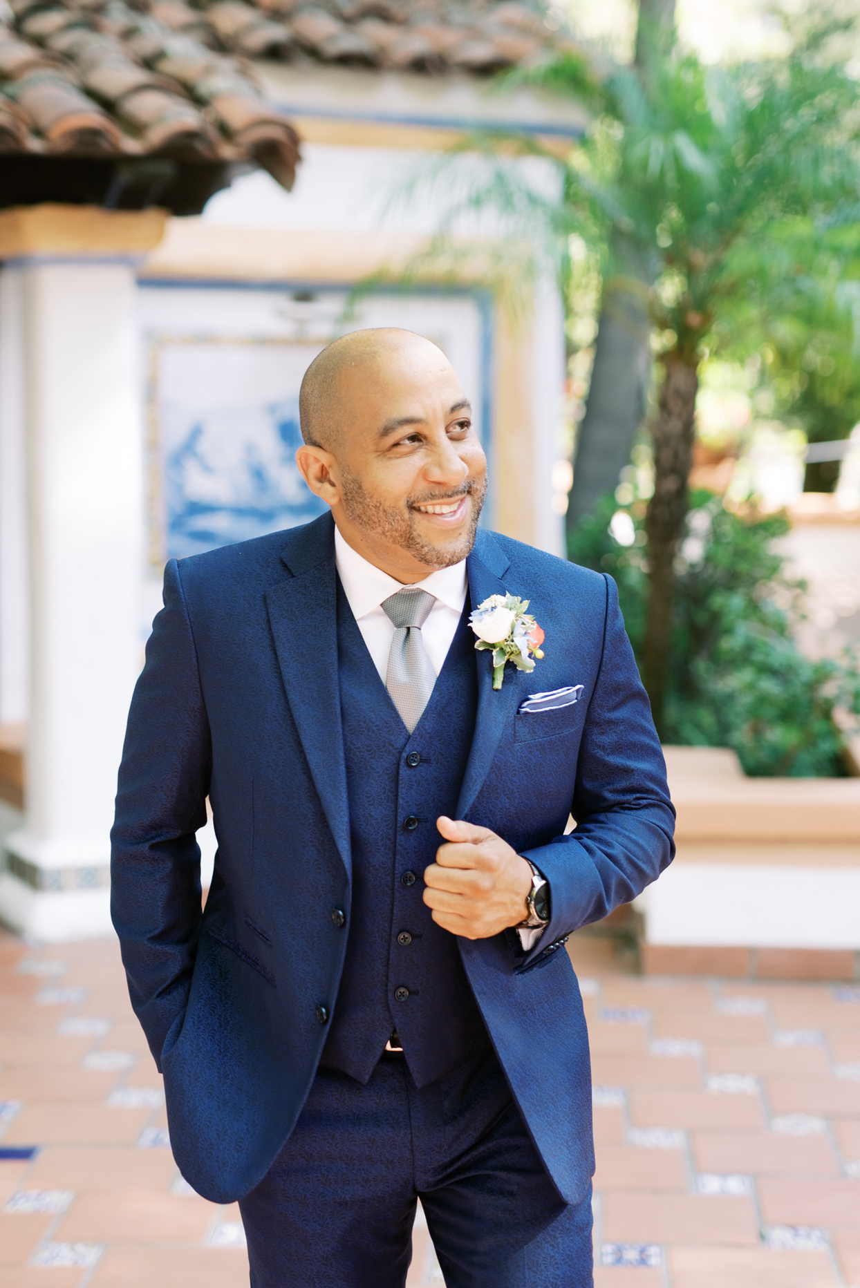 groom smiling wearing navy blue suit with silver tie