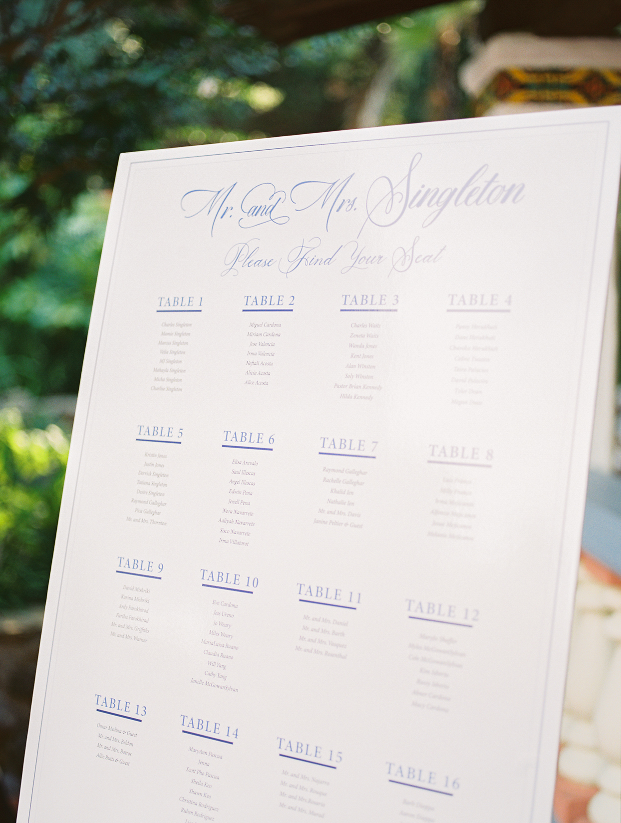 white board with blue writing wedding seating chart