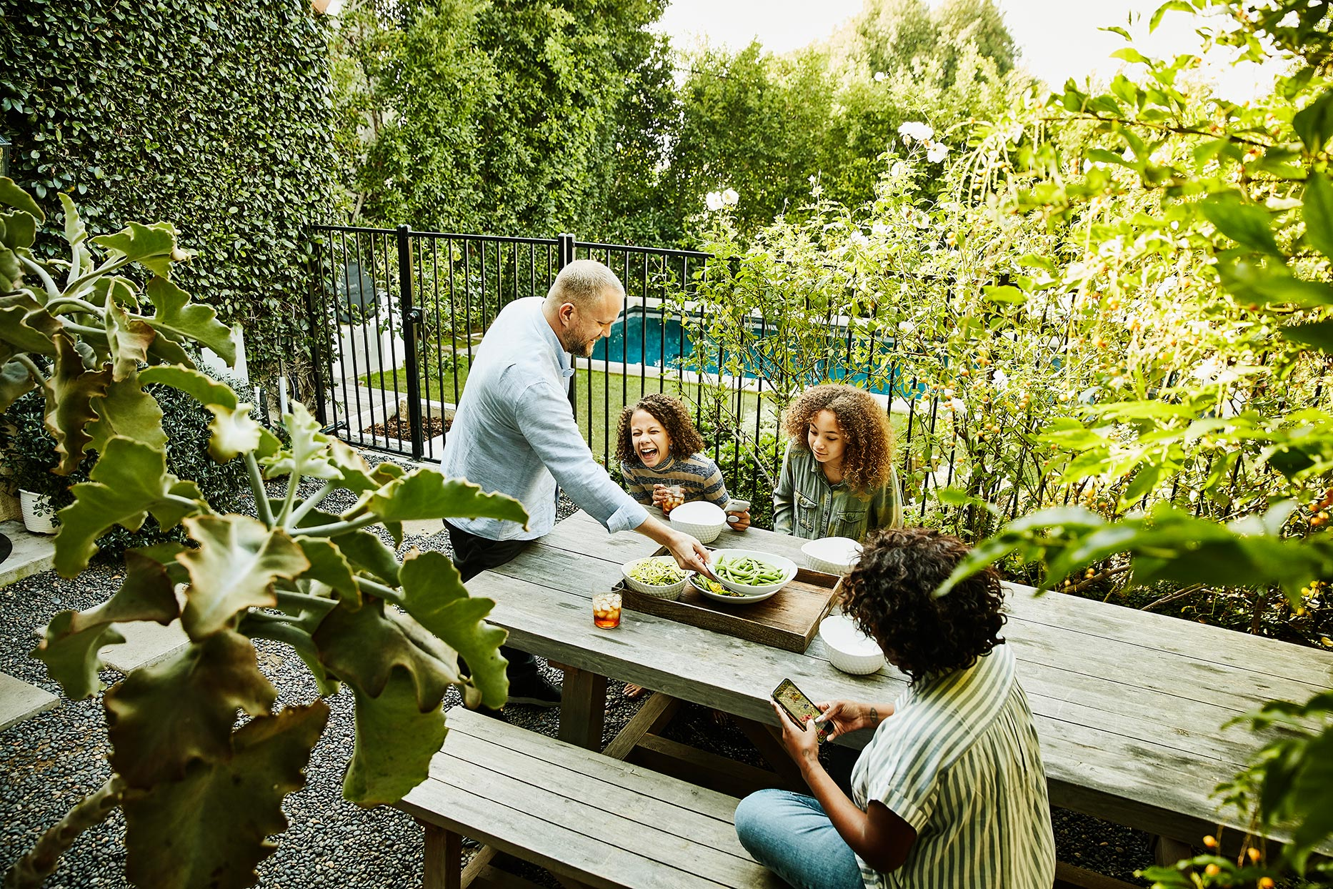 family laughing during dinner on patio