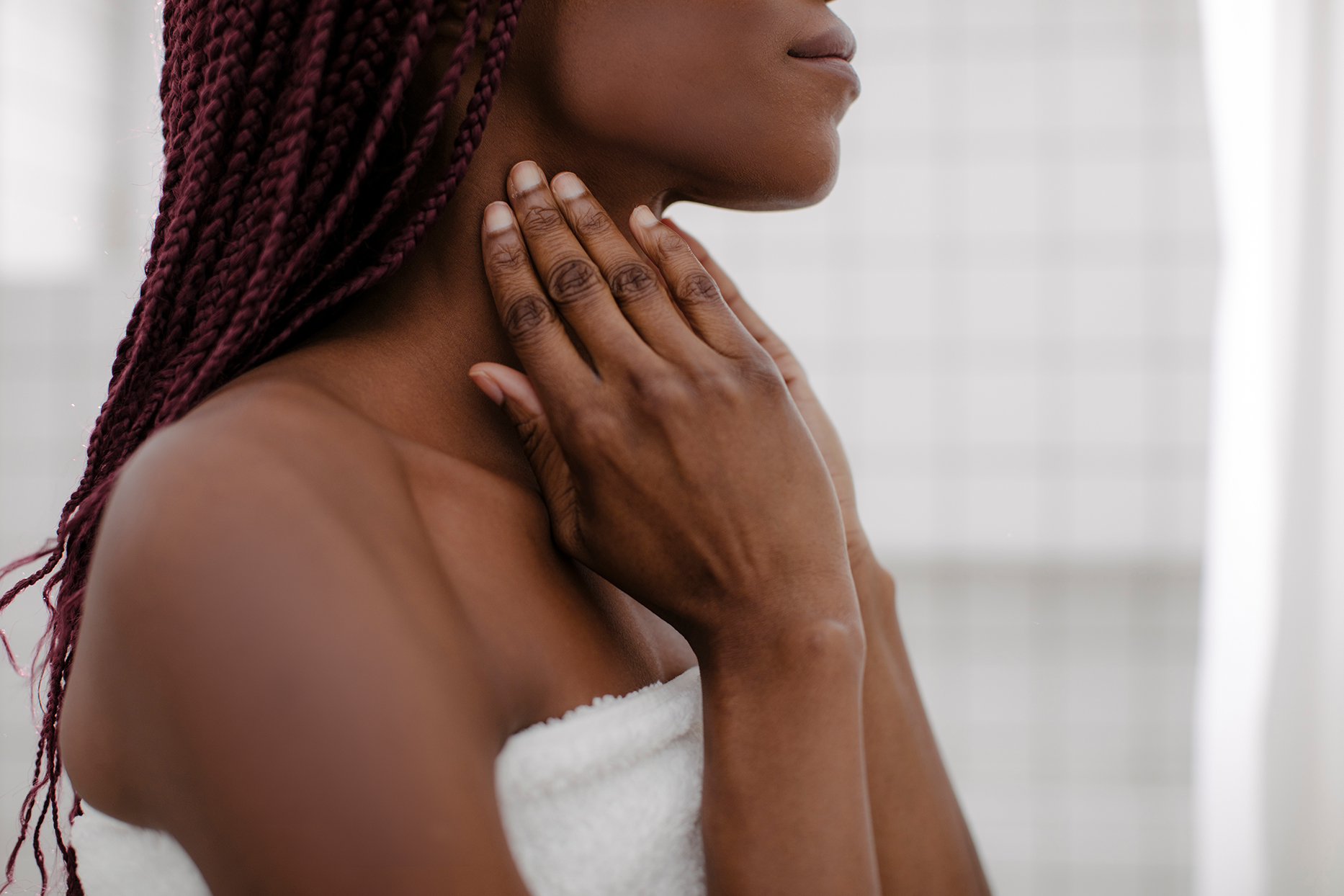 woman in towel touching neck