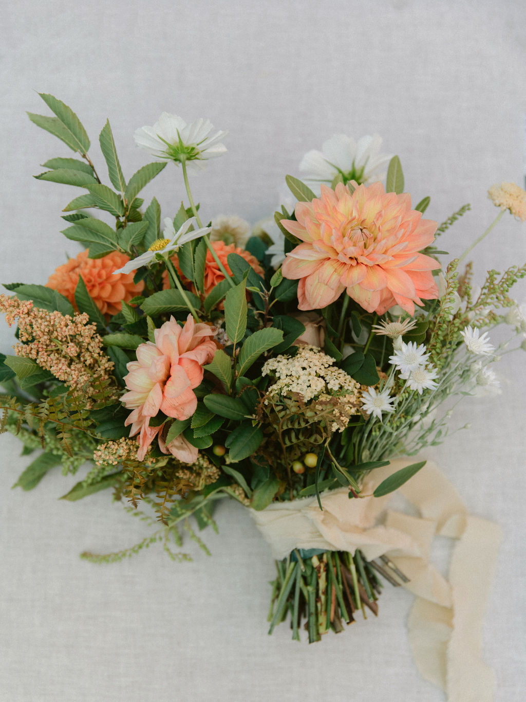 hand-tied orange dahlias and greenery bridal bouquet