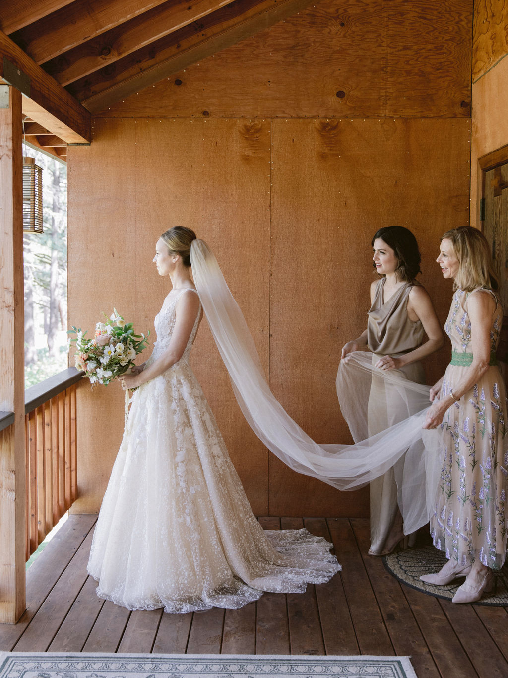 mother of the bride and bridesmaid holding brides veil