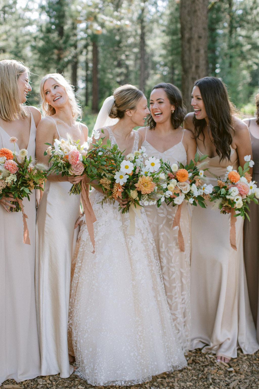 bride laughing with bridesmaids wearing mismatched champagne-colored gowns