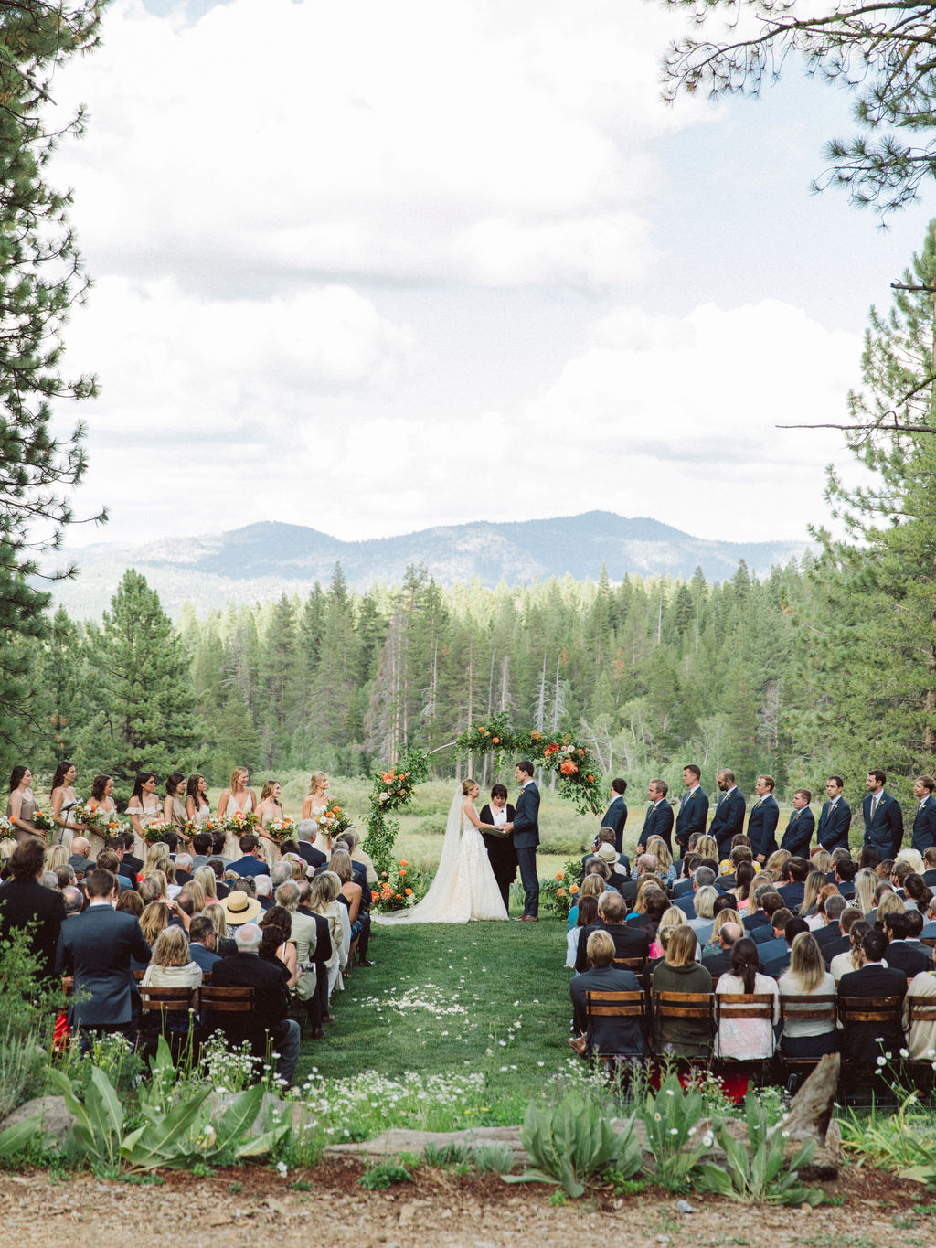 wedding ceremony with mountains and forest backdrop