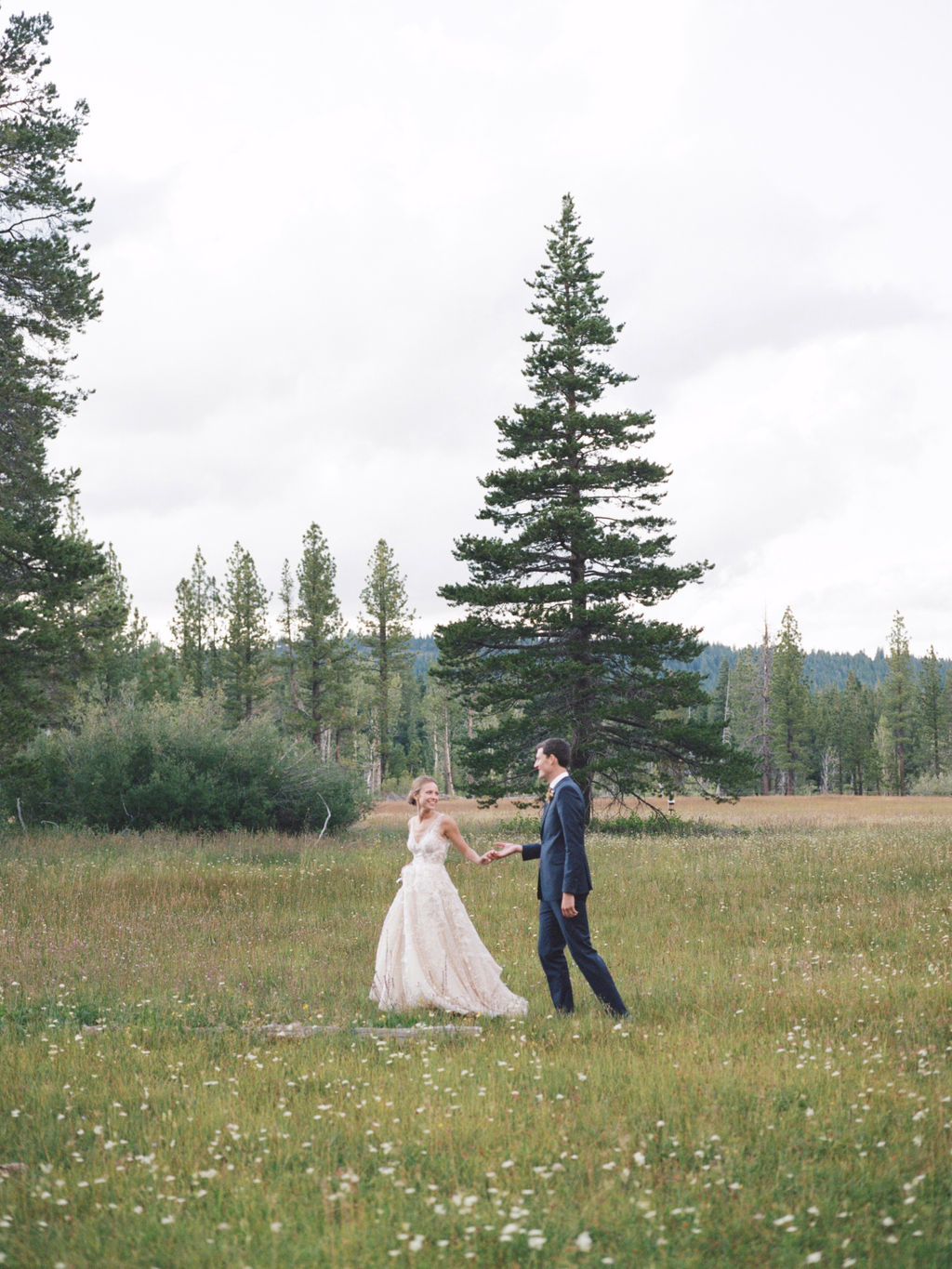 bride and groom holding hands and walking in meadow