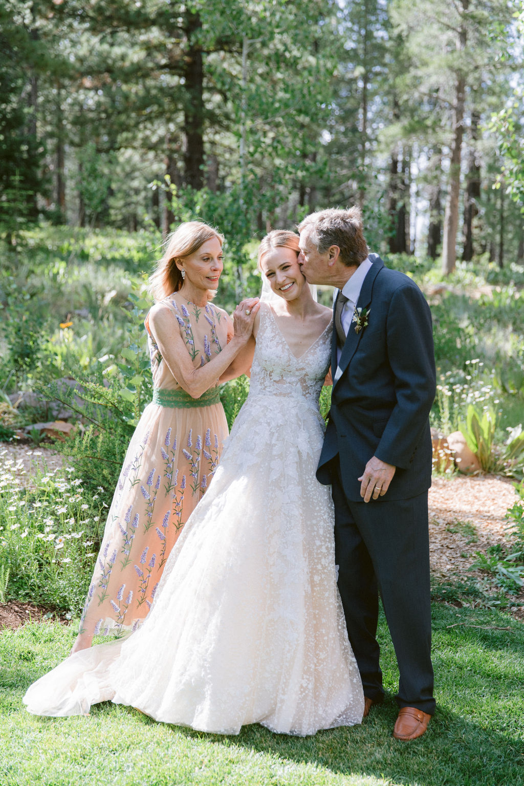 bride standing between mother and father