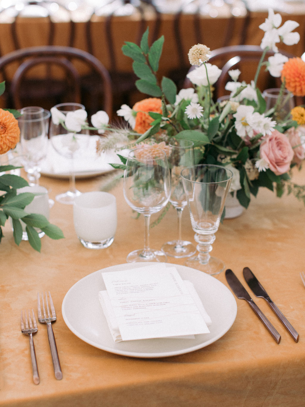wedding reception place setting with bronze flatware and ceramic plates