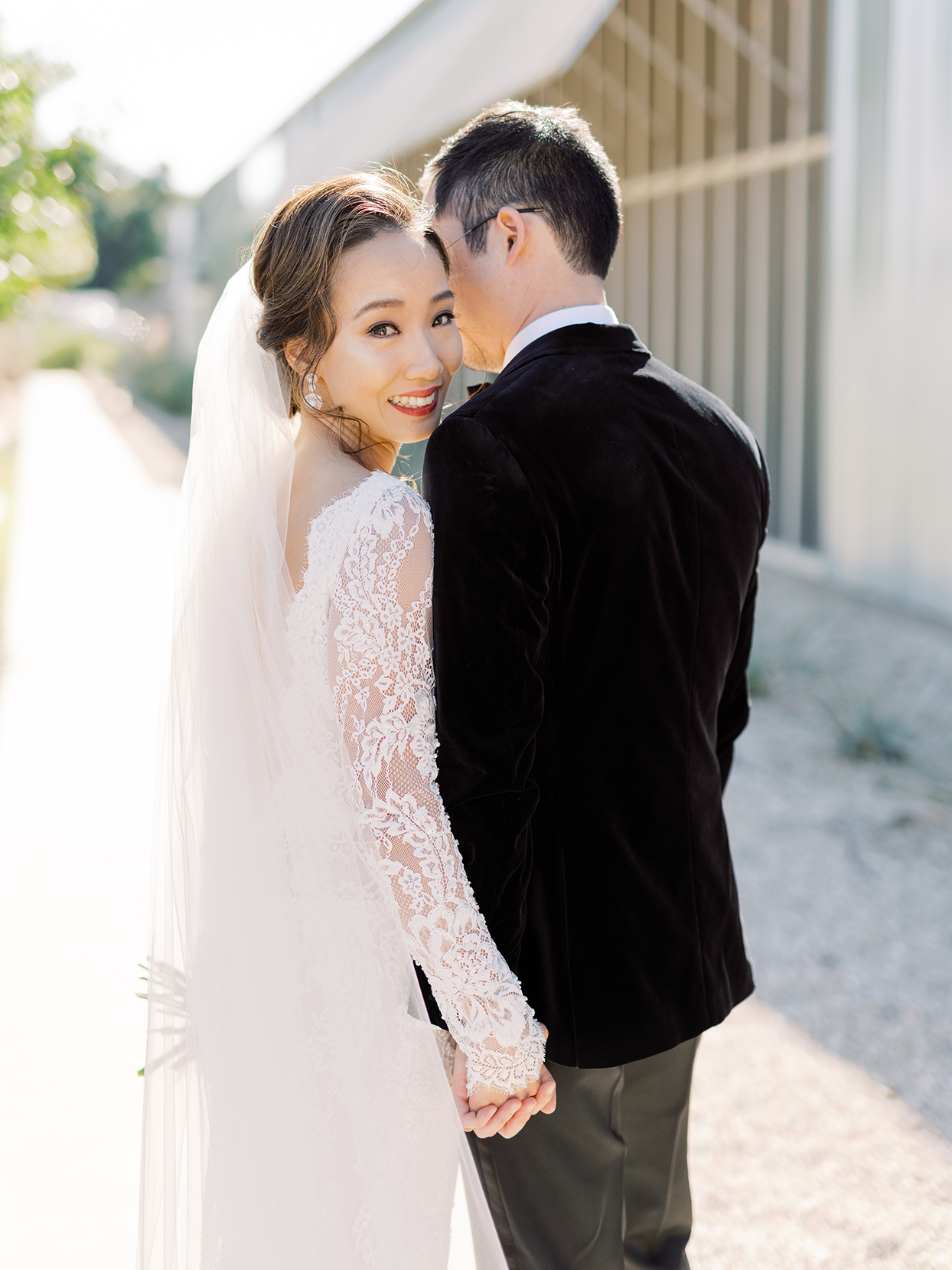 bride in white lace dress holding hands with groom for wedding portraits