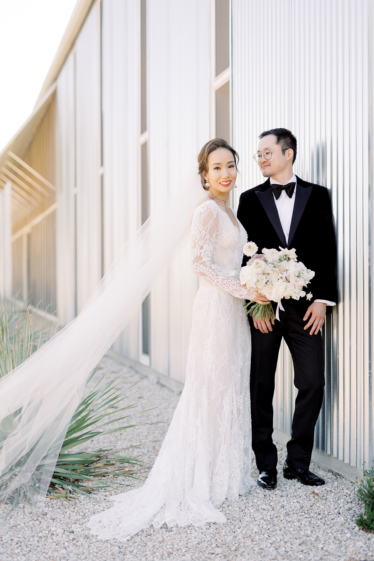 wedding couple posing against modern metal siding