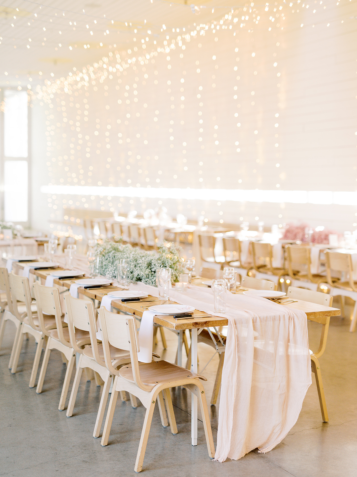 light elegant wedding reception long tables with fairy lights hanging above