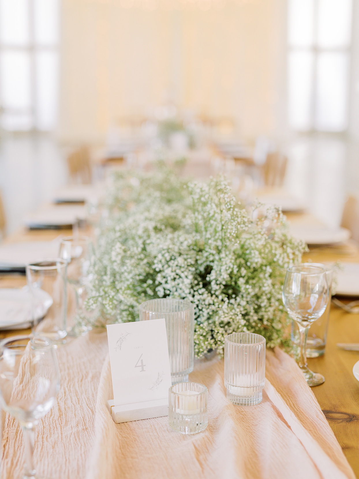 white wildflower and votive centerpieces on wooden long table