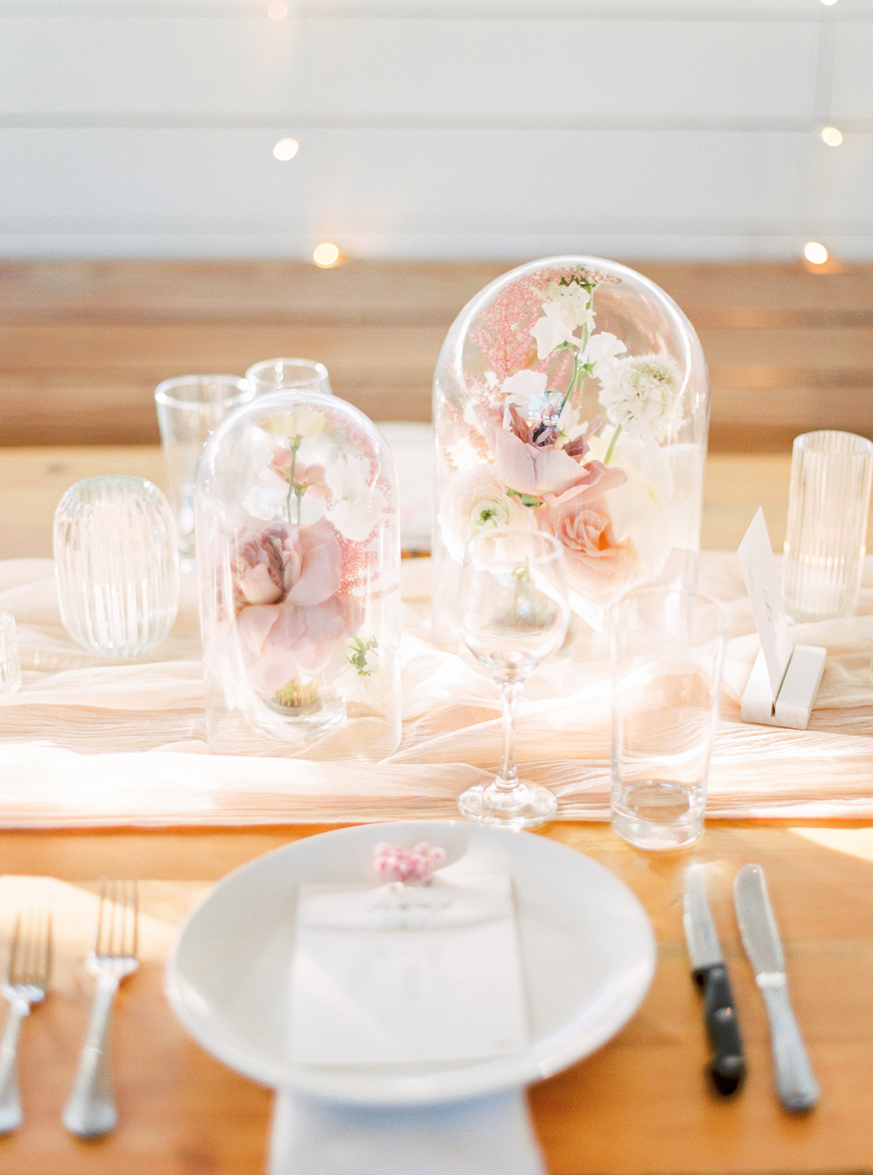 wedding reception table setting with pink flowers in cloches