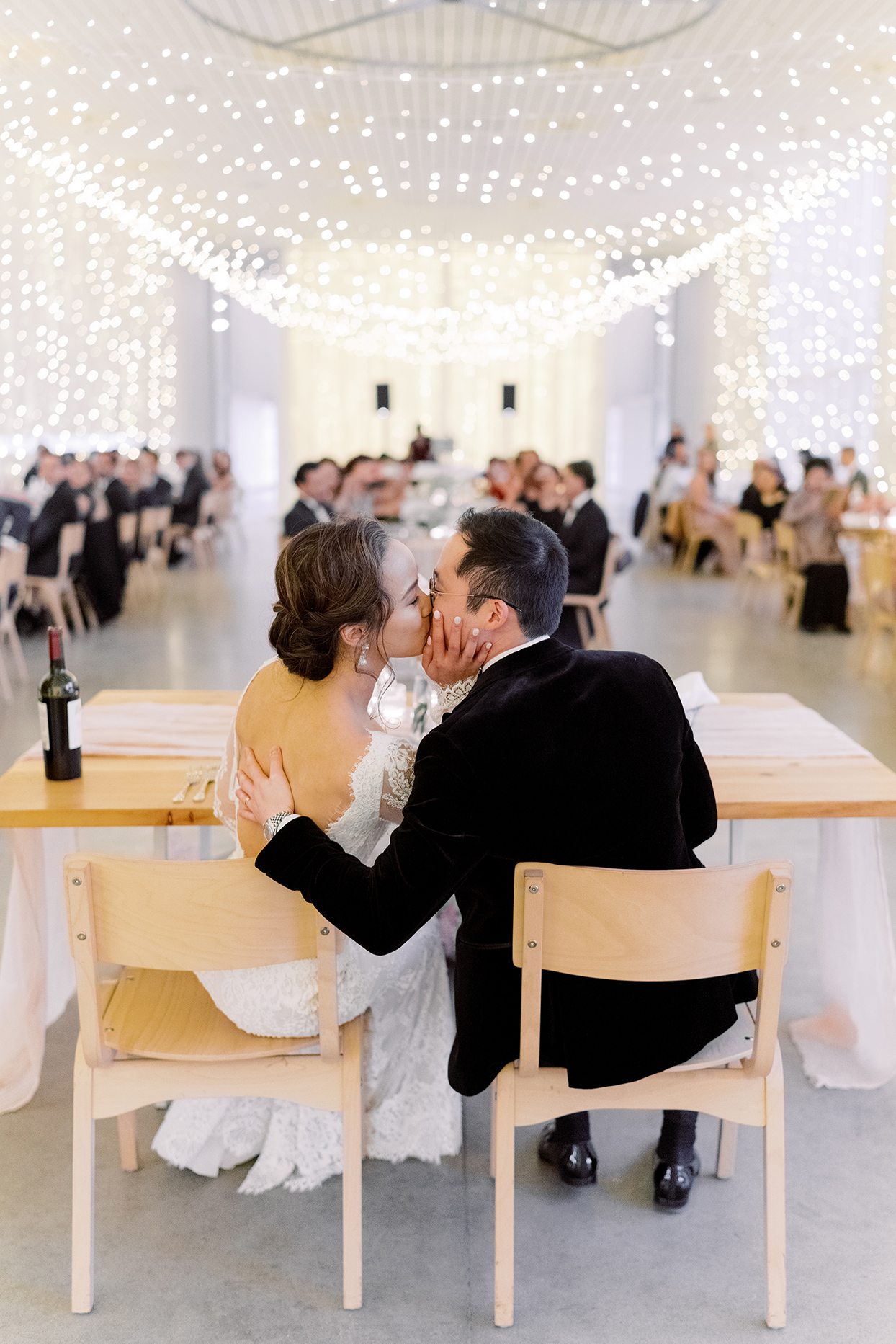 couple kissing at sweetheart table overlooking wedding reception space